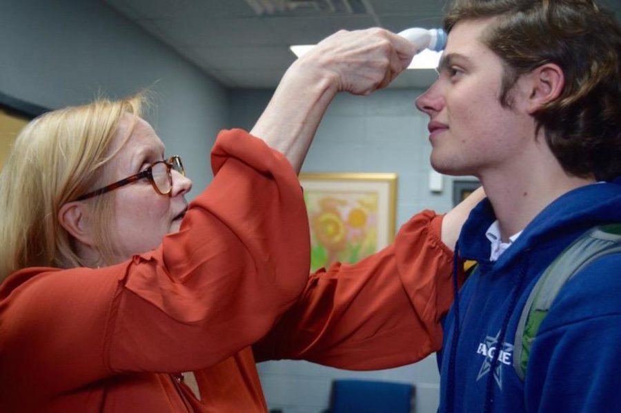 Senior Loy Sheridan has the temperature of his forehead checked by Robin Schorr.