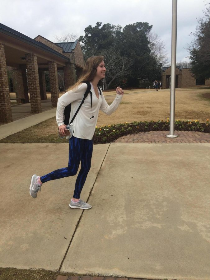 Senior Riley Grossnickle running to class in her fitness attire. (Photo by Lizzi Clayton)