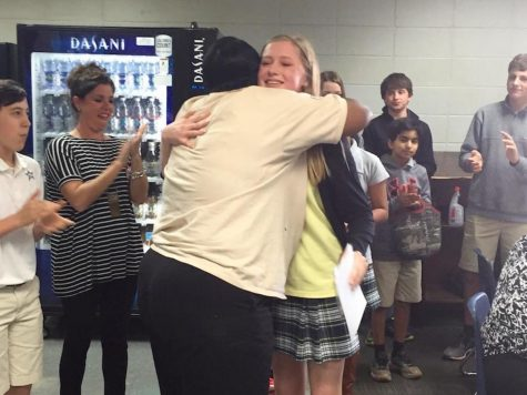 Keisha Tucker, a member of the FLIK lunchroom staff, gives Kacey Cross a hug as students and teachers applaud.