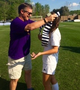 Soccer parent Johnny Peterson gives his daughter Ellie her scarf after the game against Dooly County