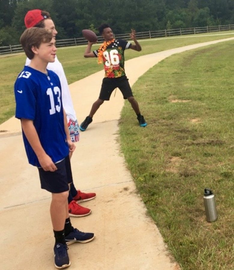 Jabin Ford tosses a football as classmates look on.