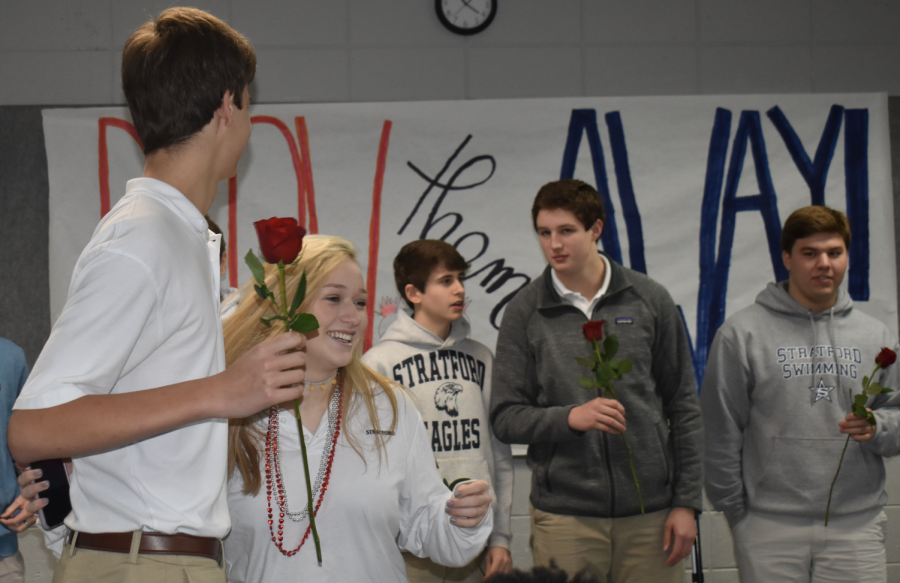Yearbook staff member Molly Groves present a rose to junior Griffin Matson