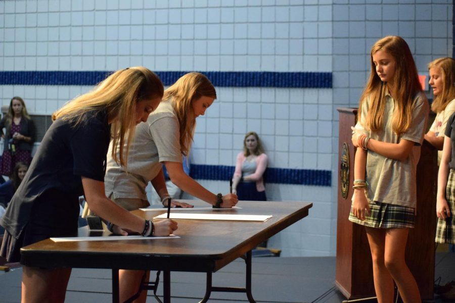 Freshmen Harley Anne Shurling and Carly Blackwood sign the honor code as Katie Beth Powers looks on