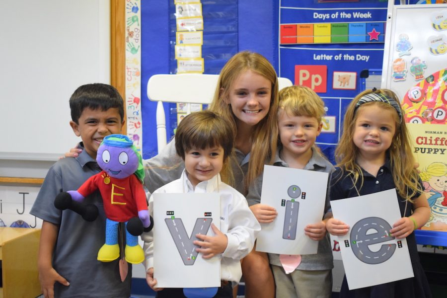 3K students (L-r) Winston Jeshuran, Asher Smaha, Davis Brown and Mallie Griffith help Evie Tharpe with her name