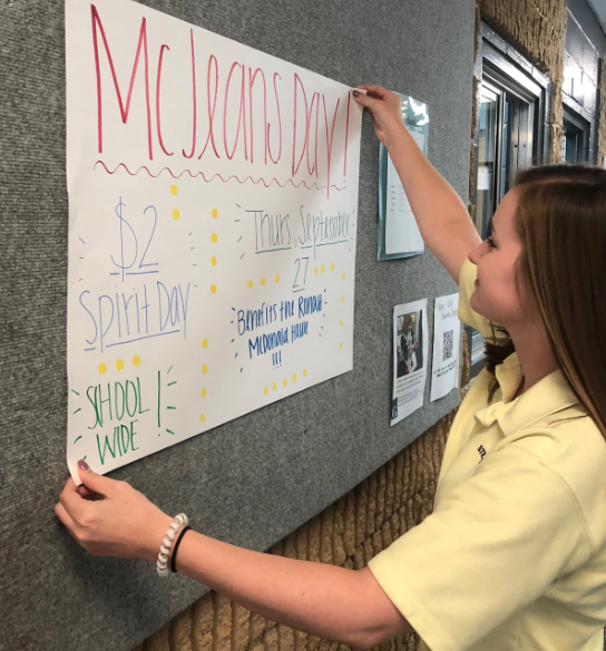 Senior Holland Schell puts up a poster promoting McJeans Day