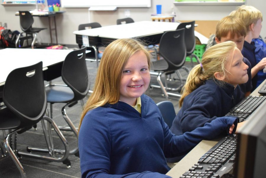 Katy Brust smiling as she is doing her classwork