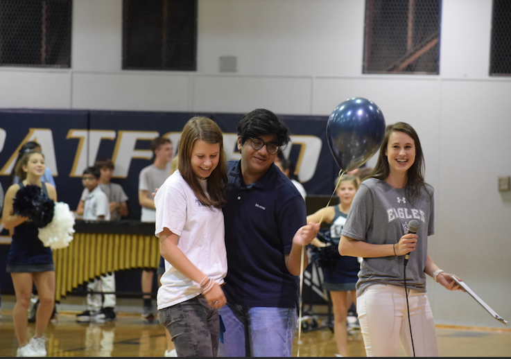 Freshman+representative+Milind+Rugnath+gets+a+hug+from+Shorter+McCook+at+Friday%27s+pep+rally+as+science+teacher+Ms.+Kinsey+Peterson+looks+on.