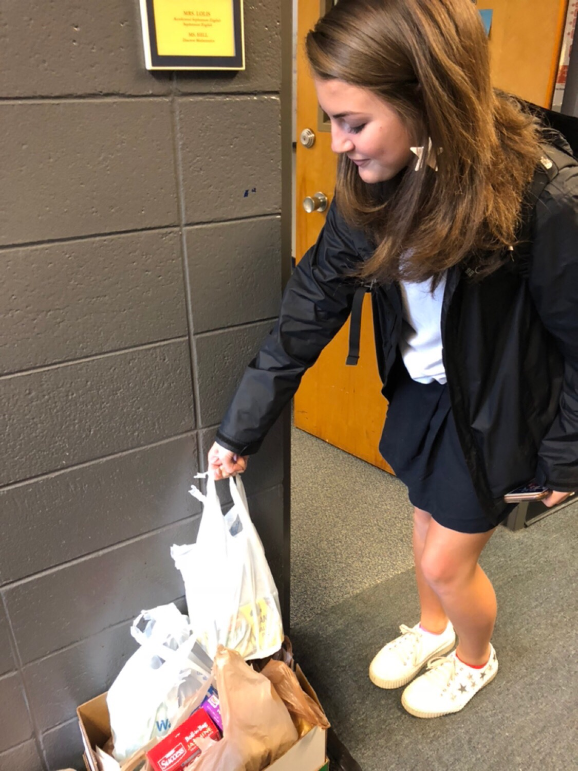 Senior Hadley Neal donates cans to her homeroom.