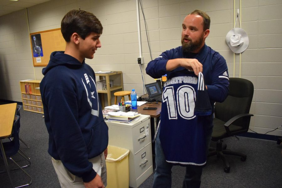 Coach Iain Jones shows soccer jersey to James Michael Reeves