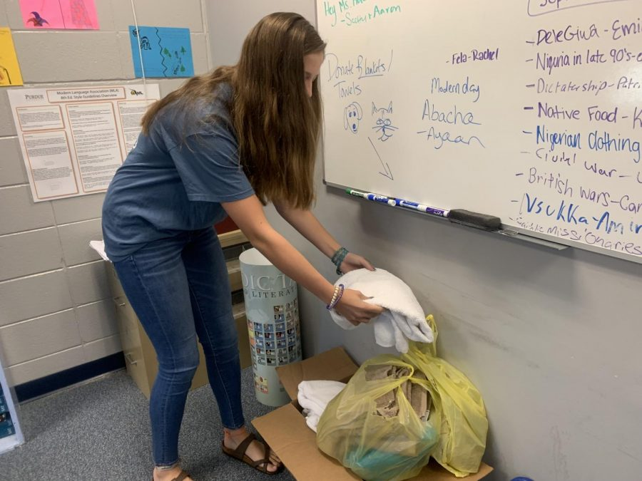 Sophomore+Emily+Hunt+donates+an+item+to+the+drive+box.