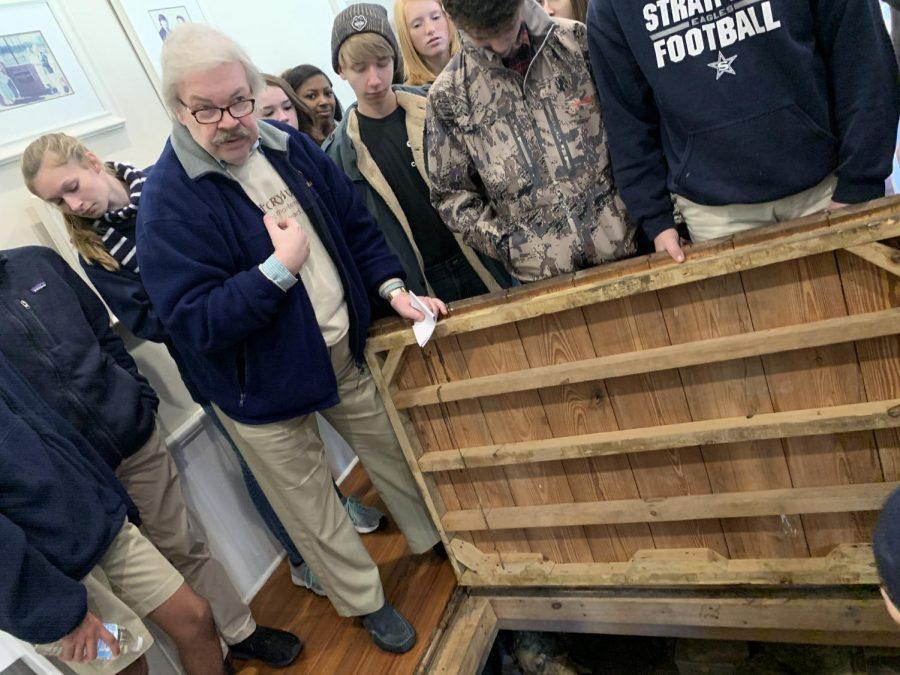 Mr. Lawson showing secret door inside the house. Freshman students taking a look inside.
