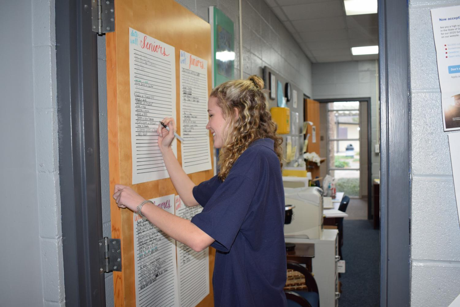 Senior Holly Hint signs up for the date wall