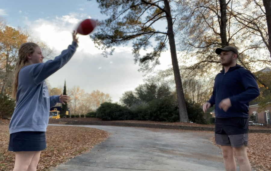 EmmaJane Canady tosses football in yard with her brother, Carter