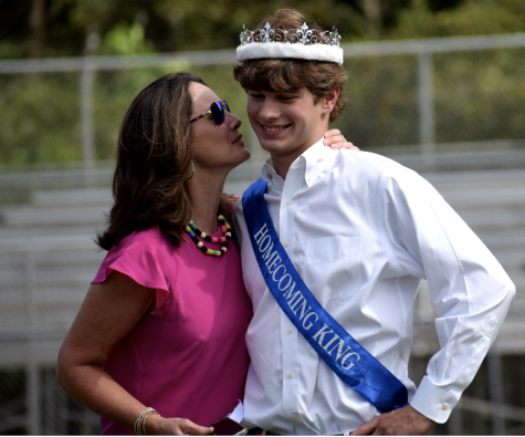 Senior, Ben Jamison bashfully accepts a kiss from his mother, Melis Jamison, after being crowned 2020-2021 Homecoming King.