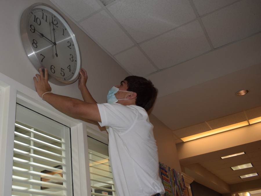 Senior James Michael Reeves checks out large clock behind circulation desk in Olson Library