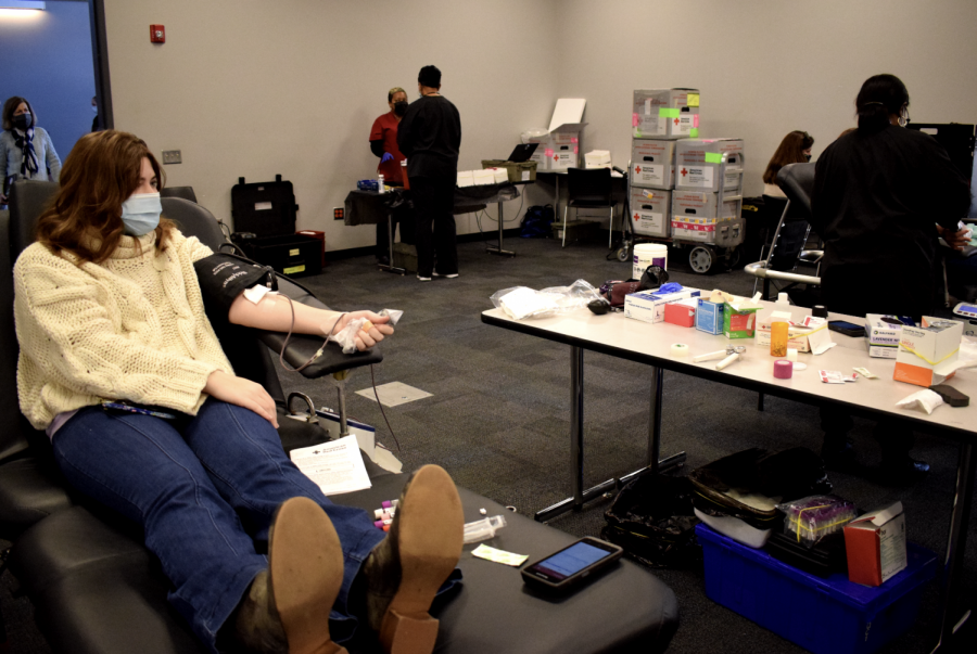Senior Carson Butcher, left, donates blood during Friday's blood drive in the Science Center